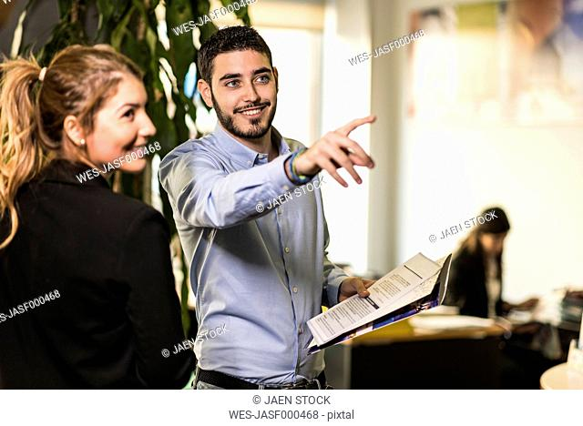 Smiling man with woman in office looking at something