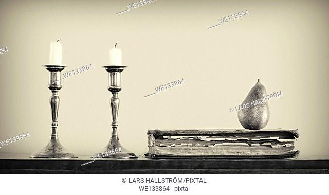 Still life with candles, book and pear