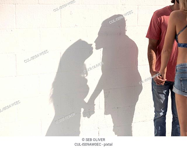 Sunlit shadow of young couple holding hands and kissing