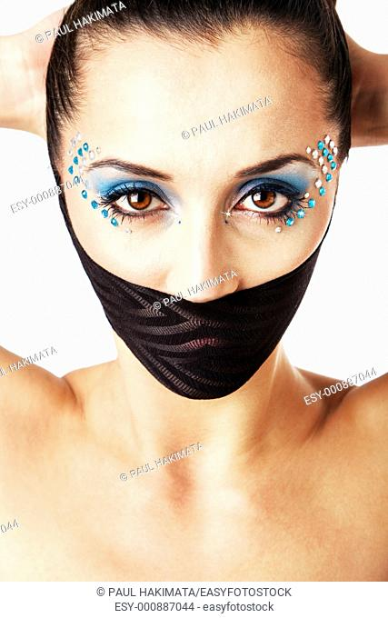 Beautiful female fashion face with blue makeup and gems rhinestones of a Caucasian Hispanic woman with hands behind head and bare shoulders and mouth covered...