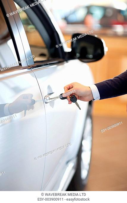 Man inserting a car key in the lock in a garage