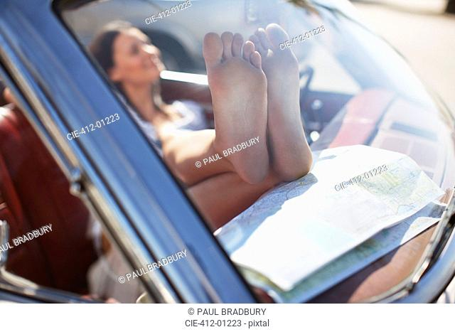 Close up of woman's dirty feet on dashboard