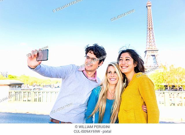Friends in front of eiffel tower taking selfie