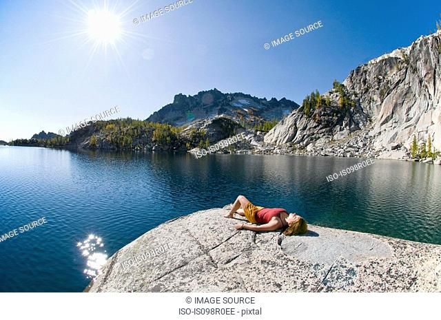 A woman sunbathing next to enchantment lakes