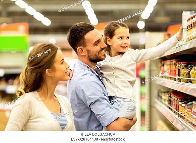 sale, shopping, consumerism and people concept - happy family with child buying food at grocery store or supermarket