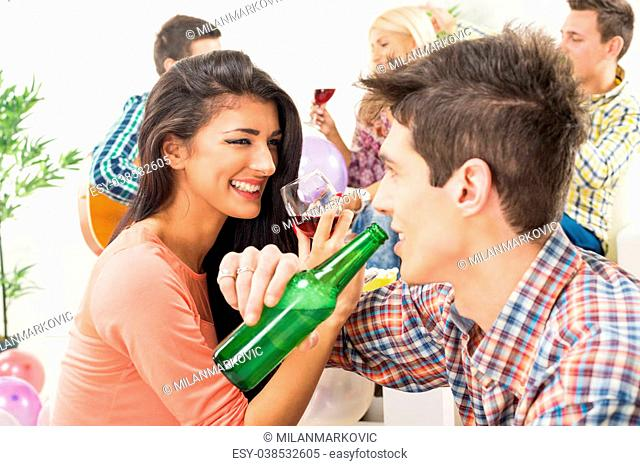 A young girl and guy at home party, drinking with crossed arms, smiling looking at each other, in the background you can see their friends who are sitting on...