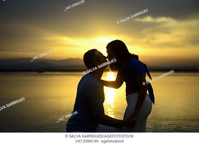 A couple of lovers kiss in the natural park of Albufera at the time of the sun