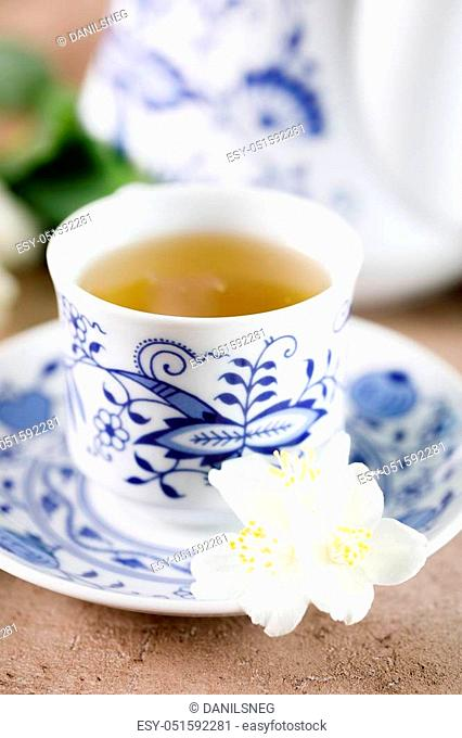 A cup of green tea with a taste of jasmine. Jasmine flowers for decoration