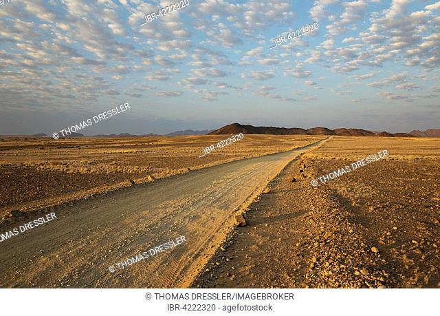 Gravel road on arid plain, isolated mountain ridges, fluffy clouds at edge of Namib Desert, evening light, Kulala Wilderness Reserve, Namibia