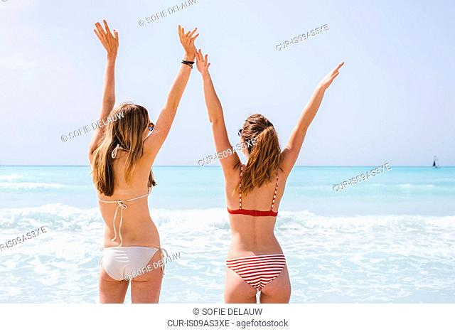 Rear view of two young female friends wearing bikinis with arms raised on beach