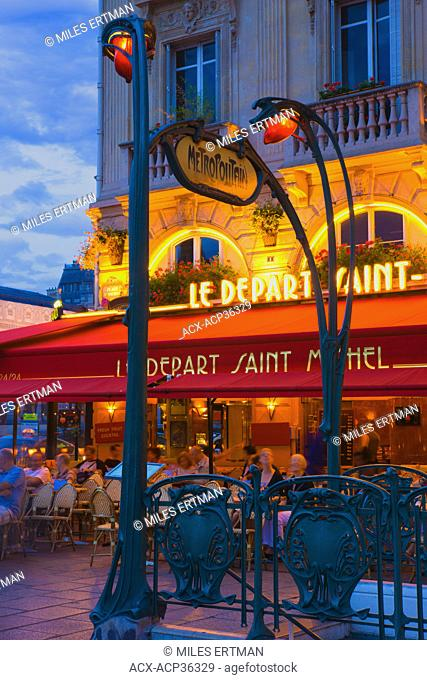 People enjoying the city streets at an outdoor restaurant in the Latin Quarter, Paris, France