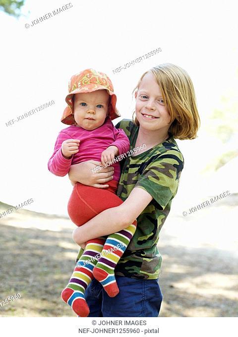 Boy holding sister