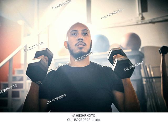 Man using dumbbells in gym