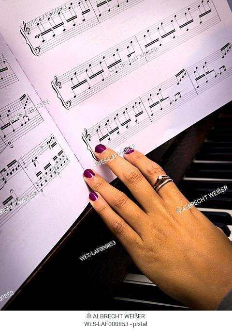 Young woman playing piano with musical notes, partial view