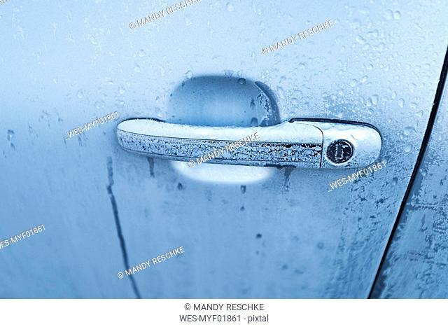 Frozen door handle of a car, close-up