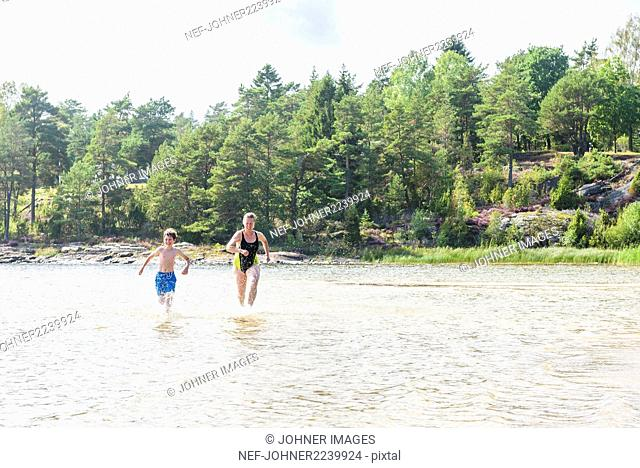 Mother and son running through water