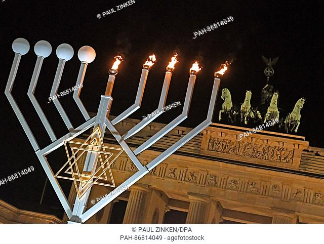 The first candles burn on a menorah for the Jewish holiday of Hanukkah in front of the Brandenburg Gate in Berlin, Germany, 27 December 2016