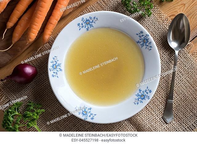 Chicken stock in a white plate, with carrots, onions and parsley in the background, top view