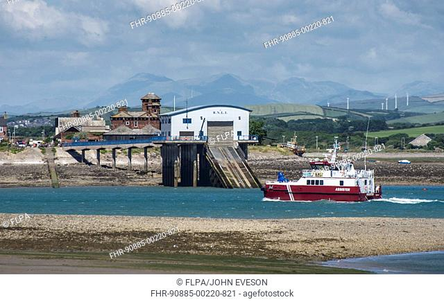'Assister' offshore tug and supply ship entering port through Piel Channel, past Roa Island and RNLI lifeboat station, Barrow-in-Furness, Cumbria, England, July