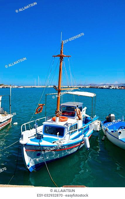 Greek fishing boat in Sitia. Traditional Greek boat in white and blue colors bobs on the waves on a clear sunny day. Port of Sitia, Crete
