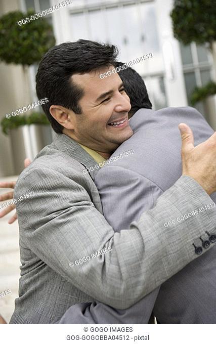 Businessmen hugging