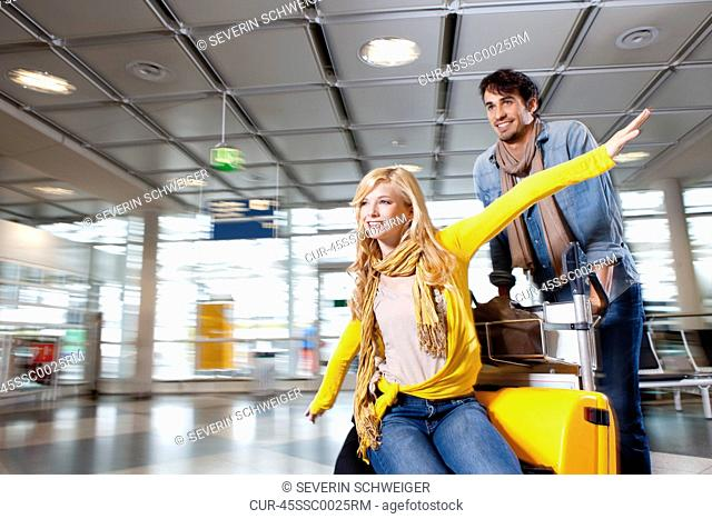 Couple playing with luggage in airport