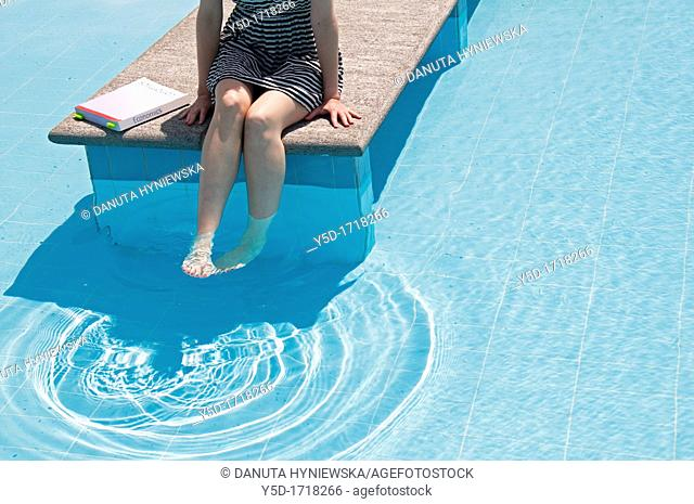 young woman trying to study Economics at the swimming pool