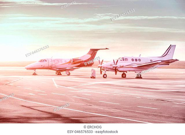 Private jet planes parking at the airport. Business aircrafts at sunset