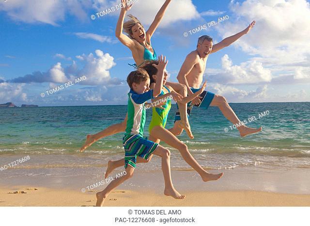 A family of four on the beach on a hawaiian island; Kailua, Island of Hawaii, Hawaii, United States of America