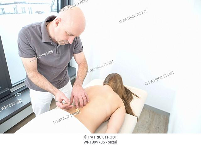 Acupuncturist Lighting a Moxa Cone