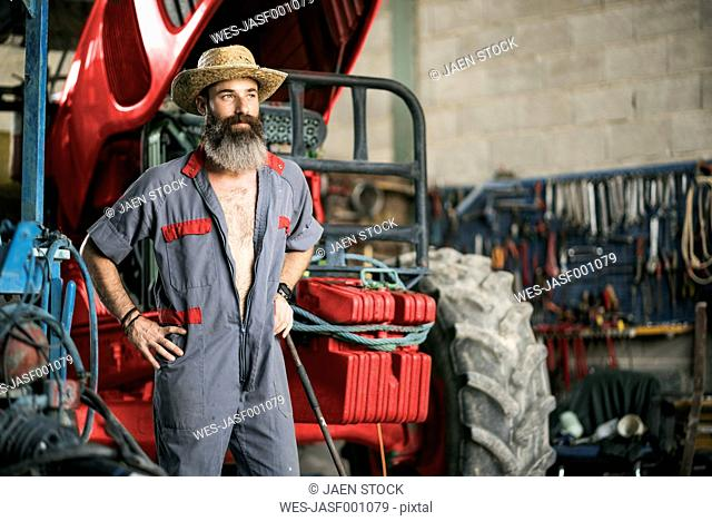 Portrait of confident mechanic with hat at tractor