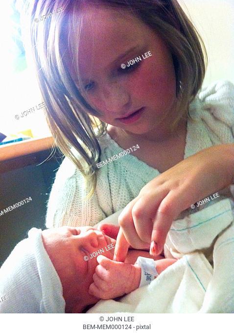 Caucasian girl looking at newborn baby