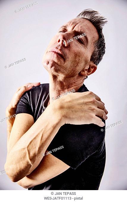 Portrait of egocentric mature man hugging hisself