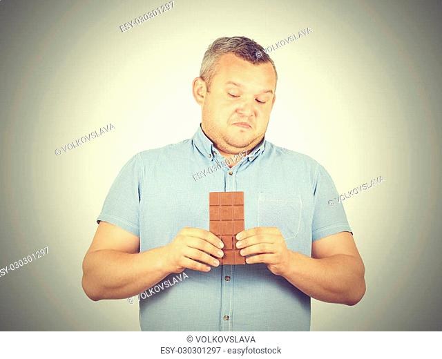 fat man refuses to chocolate. Diet, overweight, healthy food isolated on background