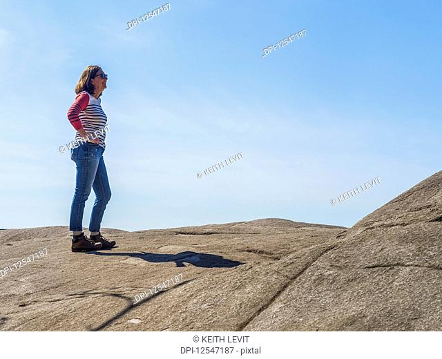 A woman stands at Quarry Rock on the Baden-Powell Trail against a blue sky, Deep Cove, North Vancouver; Vancouver, British Columbia, Canada
