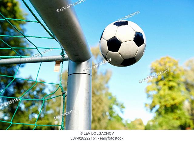 sport, soccer and game - ball flying into football goal net