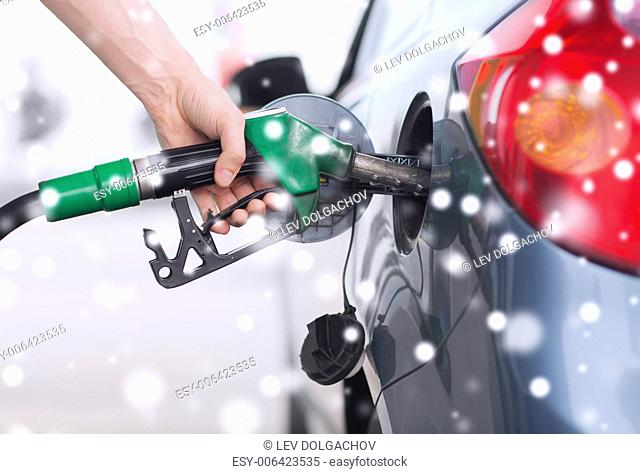 transportation, tanking, people and vehicle concept - close up of male hand with fuel hose nozzle tanking car