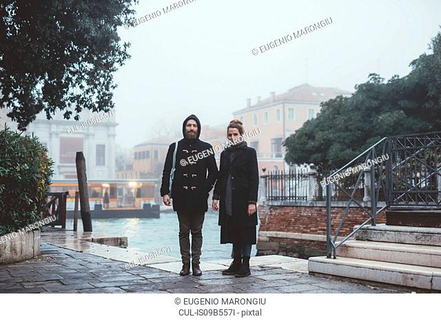 Portrait of couple standing by misty canal, Venice, Italy
