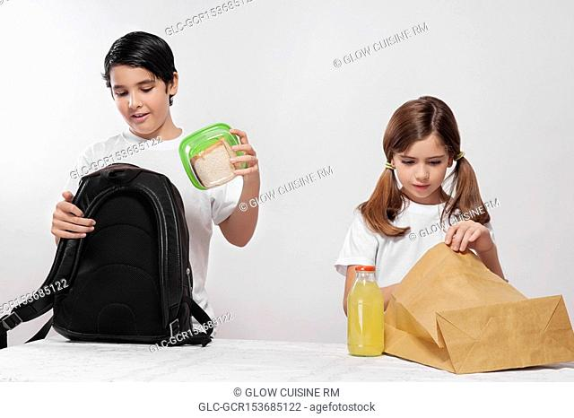 Boy and a girl packing their lunch for school