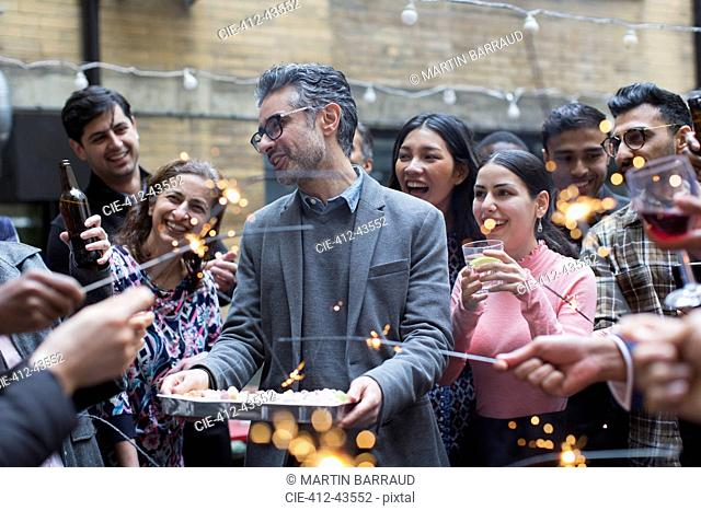 Friends with sparklers celebrating with man holding birthday cake