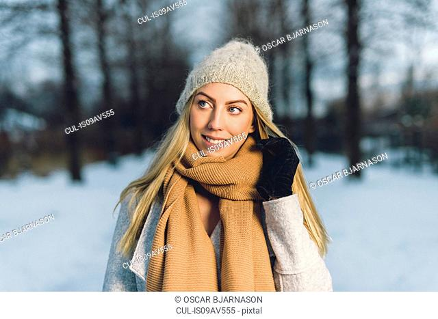Portrait of young woman in snow wearing woollen hat and scarf looking away smiling