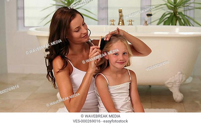 Mother brushing her little girls hair in the morning