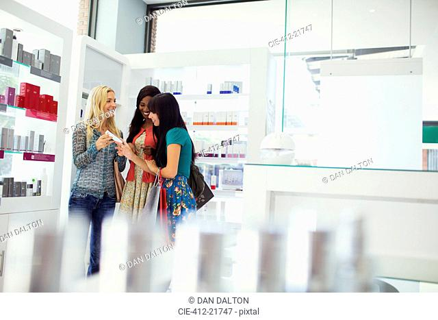 Women discussing skincare products in drugstore
