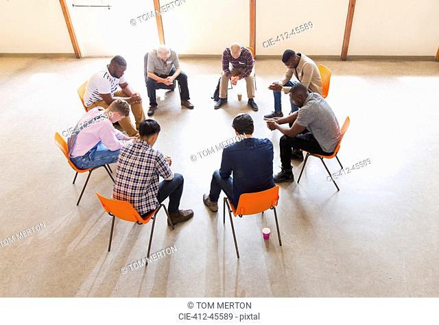 Men praying in circle in prayer group