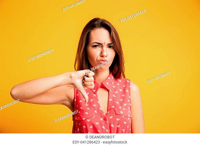 Young upset brunette woman showing thumb down gesture, looking at camera, isolated on yellow background