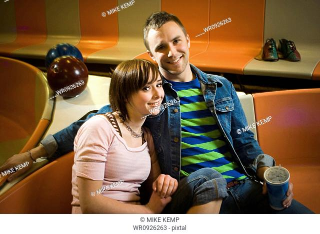 Portrait of a young man and a teenage girl sitting in a bowling alley