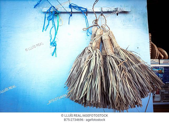 Whitewashing brushes hung on blue wall. Chaouen, Morocco