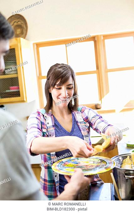 Hispanic woman serving boyfriend in kitchen