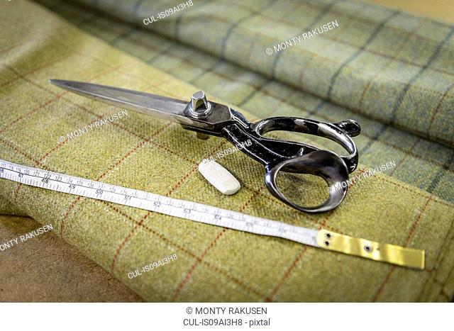 Harris tweed material and scissors in clothing factory
