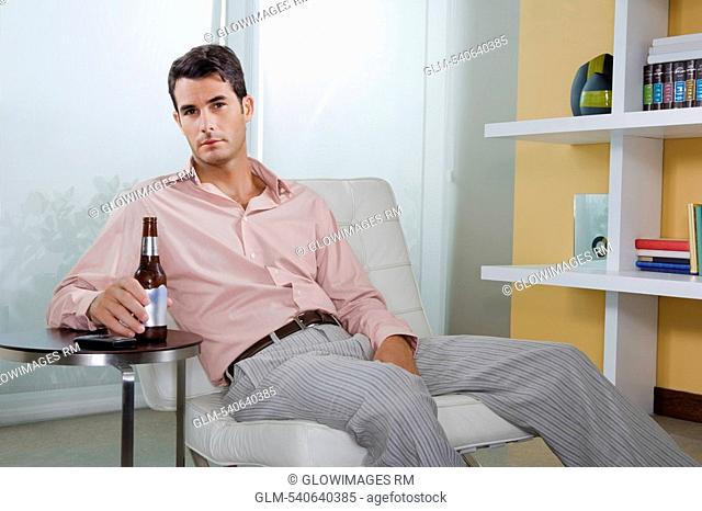 Portrait of a mid adult man sitting on a chair and holding a beer bottle
